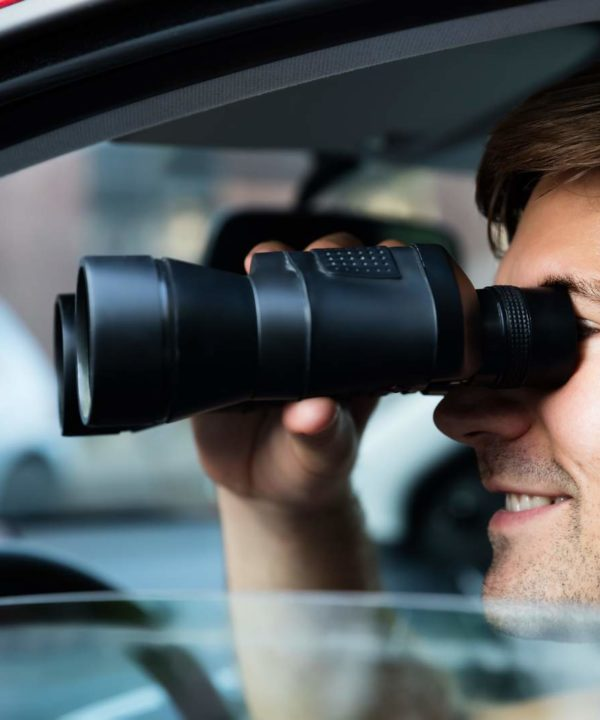 Young Male Looking Through Binoculars Sitting Inside Car